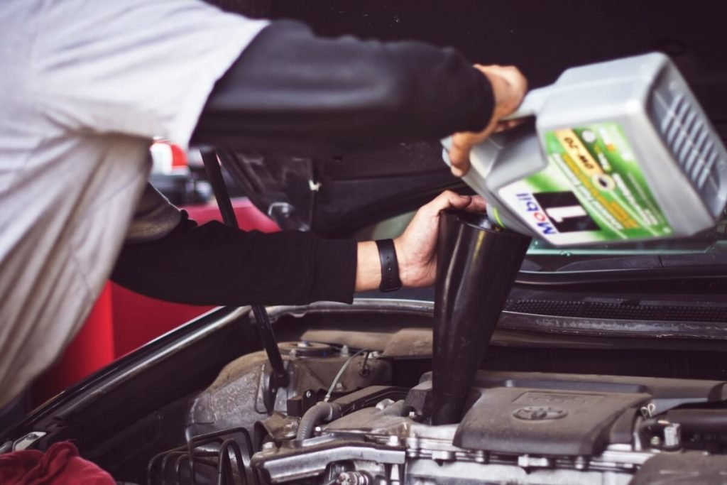 Man filling up engine with engine oil